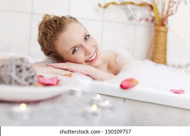 Beautiful woman relaxing in a foamy bubble bath resting her head on the side and smiling at the camera in appreciation and enjoyment