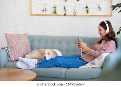 Beautiful woman relaxing at home streaming music on her portable device phone cellphone