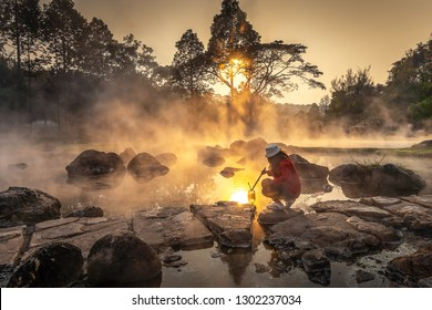 Beautiful woman relaxing in hot springs at Chae Son National Park, Hot springs over rocky terrain with misty and morning sunrise rays
