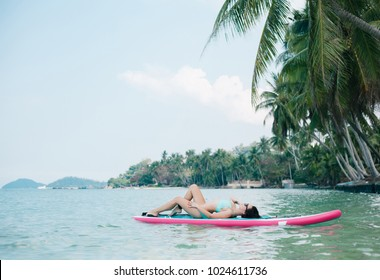 beautiful woman relaxing on paddle board on sea at tropical resort