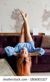 Beautiful woman relaxing on a sofa with head upside down at home