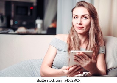 Beautiful woman is relaxing on sofa with tablet