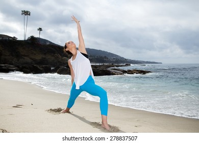 Beautiful woman relaxing and practicing yoga at beach