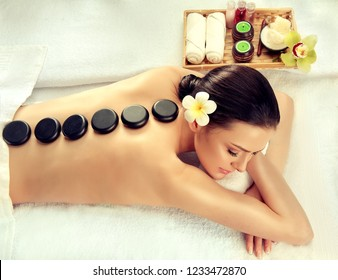 Beautiful woman relaxing in spa salon with hot stones  body massage