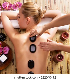Beautiful woman relaxing in spa salon with hot stones on body. Beauty treatment therapy