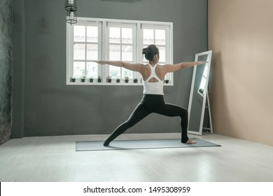 beautiful woman relaxing and stretching practicing yoga on the floor in home, yoga concept, fitness concept