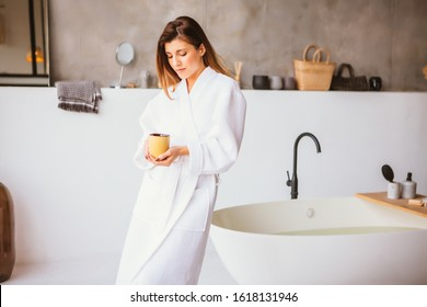 Beautiful woman relaxing in white bathrobe standing near bath with cup of tea or coffee