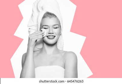 Beautiful woman removes makeup with cotton pads, standing on white background in white towel