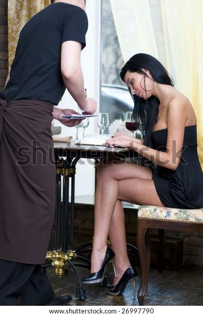 Beautiful woman in restauran. Waiter is taking order