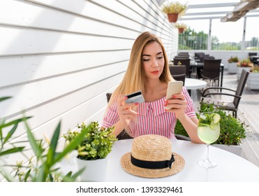 Beautiful woman in a restaurant dress, girl in summer cafe. Concept of buying and paying dinner dinner by credit card. In hand of the phone is plastic card. Online banking, online application.