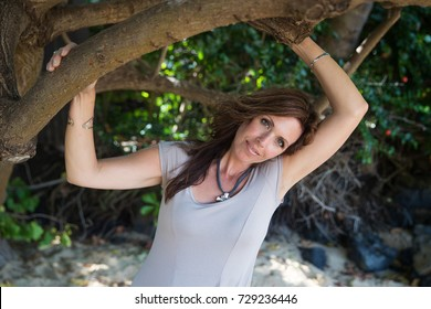 Beautiful woman resting arms on a tree branch