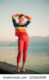 Beautiful woman resting by the lake at sunset on warm evening, wearing colorful pullover