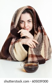 Beautiful woman resting and drinking tea wrapped in a wool plaid blanket.