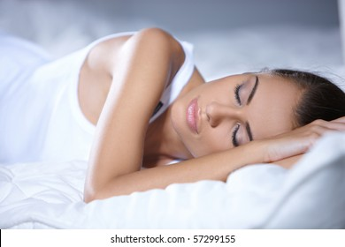 Beautiful woman is resting on white bed