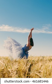 Beautiful woman in retro ball dress falling in wheat field with her blue silk skirt flying up surrounded by bright shine