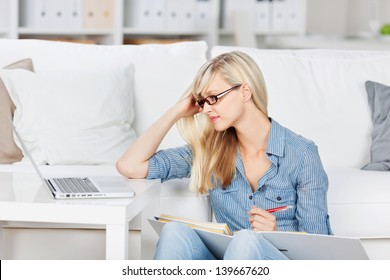 Beautiful woman reviewing her lesson with her laptop and book