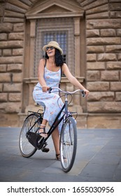 A beautiful woman rides a bicycle with a dress and a straw hat at the ancient streets of Florence Italy. Vacation concept, city tour with a bike.
