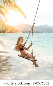 Beautiful woman is  riding a swing on the beach
