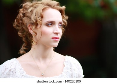 Beautiful woman with romantic bride hairstyle wearing in white wedding dress posing in interior apartment
