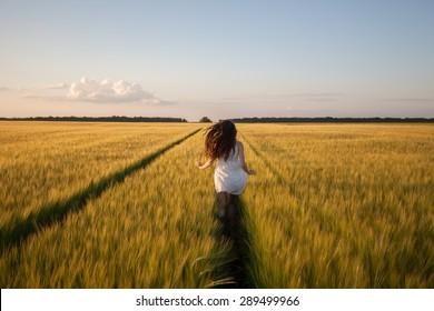 beautiful woman run away in yellow wheat field