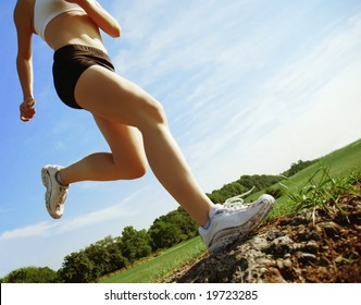 Beautiful woman runner in front of blue sky, low angle.
