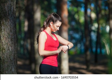 Beautiful woman runner looks at her fitness tracker getting ready for a run in the summer forest