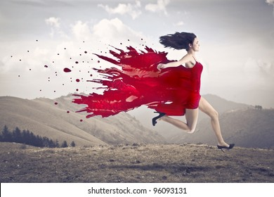 Beautiful woman running with her dress melting in red paint