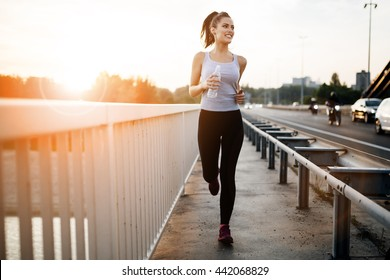 Beautiful woman running over bridge during sunset