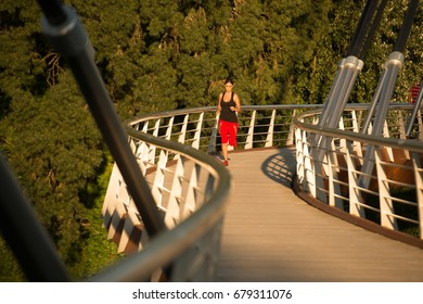 Beautiful woman running over bridge in the morning
