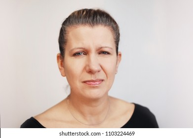 A beautiful woman with a sad irritating face on a gray background with gray hair. She is sad because her painted hair is very quickly washed off and her gray hair appears