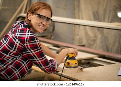 Beautiful woman in safety glasses looking at camera and holding electric sander in hands. Professional young craftswoman with ginger hair looking at camera and smiling.