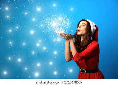 Beautiful woman in Santa hat blowing snow on light blue background, space for text. Christmas party