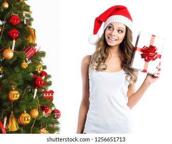 Beautiful woman in santa hat with gift near the Christmas tree. New Year or Christmas gifts.