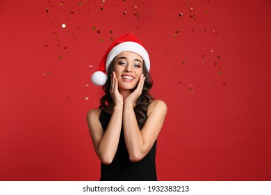 Beautiful woman in Santa hat on red background. Christmas party
