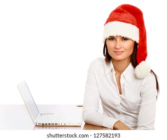 A beautiful woman in santa hat sitting on the table, isolated on white background