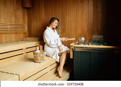 Beautiful woman in sauna pouring oils on hot stones to clean airways