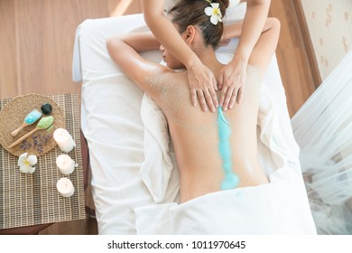 Beautiful woman with scrub Get a massage with sea salt in the spa salon.