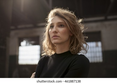 Beautiful woman with a serious expression on her face looking straight ahead with a view of industrial area  in the background