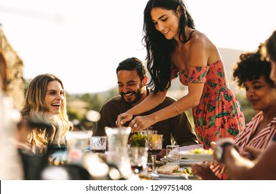 Beautiful woman serving food to friends sitting at dinner table. Group of friends having a party together outdoors.