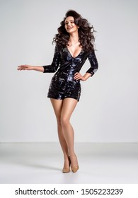 Beautiful woman with a sexy slim body.  Beautiful stunning girl  with curly hairstyle. Beautiful woman with a perfect legs.   Fashion model. Gorgeous sensual woman in a black shiny  dress.