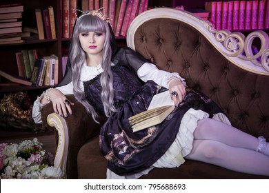 A beautiful woman in the shape of a lolita, a doll with cat ears sitting on a sofa in a library with a book in her hands and reading. Japanese street fashion. A doll in a dress. Copy space.