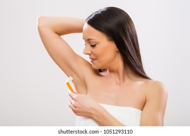 Beautiful woman shaving under her arm .