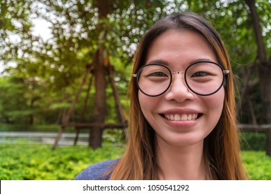 beautiful woman She wears black spherical glasses and she smiles.Her eyes are large.Copy space.