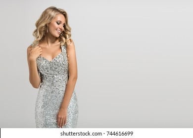 Beautiful woman in shining silver dress on gray background.