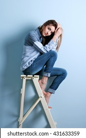Beautiful woman in shirt and jeans sitting on a ladder on blue wall background