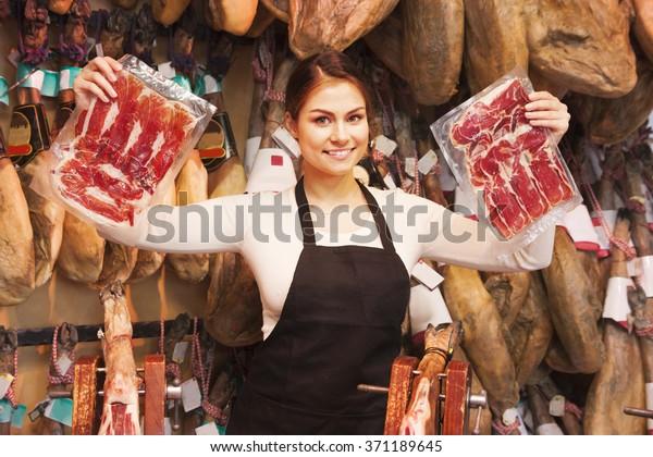 Beautiful woman in a shop selling jamon