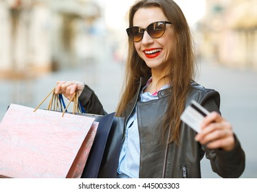 beautiful woman with shopping bags and credit card in the hands on a street