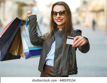 Beautiful woman with shopping bags and credit card in the hands on a street- Let's go shopping concept