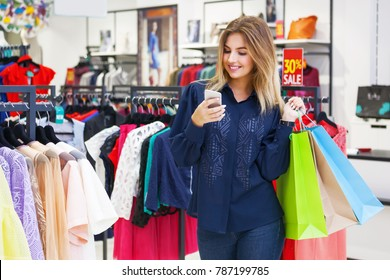 Beautiful woman with shopping bags looking at her phone while going out on a shopping spree.