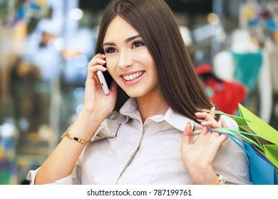 Beautiful woman with shopping bags talking on the phone while going out on a shopping spree.